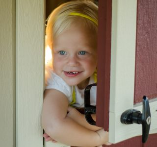Child opening door in kids playhouses for sale in texas