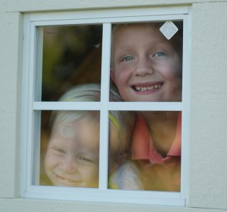 Children looking from window of kids playhouses for sale